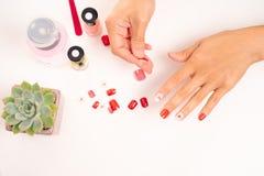 Mulheres tratamento de mãos e diplomatas que um prego dá forma durante o procedimento de extensões do prego com gel em casa Conce Imagens de Stock