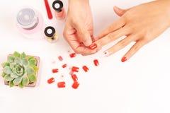 Mulheres tratamento de mãos e diplomatas que um prego dá forma durante o procedimento de extensões do prego com gel em casa Conce Imagens de Stock Royalty Free
