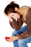 Mulheres tristes que prendem o coração em sua mão. Fotografia de Stock