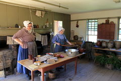 Mulheres vestidas como os peregrinos, demonstrando a vida na cozinha, vila velha de Sturbridge, massa de Sturbridge, em setembro  Imagens de Stock Royalty Free