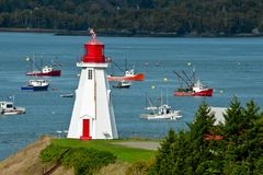Mulholland Point Lighthouse. A fishing fleet plies the waters behind the Mulholland Point Lighthouse. Campobello Island, New Brunswick, Canada stock images