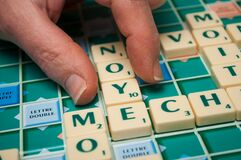 hand of woman playing with plastic letters to forming a word on Scrabble board game