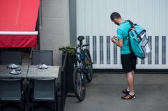 Delivery man waiting with smartphone near restaurant, deliveroo is a british delivery company in mountain bike stock photos