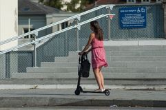 Portrait of attractive girl with red dress on scooter in front of the train station stock image