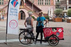 Portrait of girl hostess from Tourist Office at information stand with tricycle stock photography