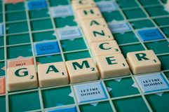 Closeup of plastic letters with words gamer and chance on Scrabble board game. Mulhouse - France - 2 December 2018 - Closeup of plastic letters with words gamer royalty free stock photo