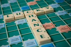 Closeup of plastic letters with words lucky and chance on Scrabble board game. Mulhouse - France - 2 December 2018 - Closeup of plastic letters with words lucky royalty free stock photography