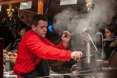 Man serving churros at the christmas market Royalty Free Stock Photo