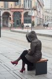 Black woman waiting the tramway on bench with smartphone. Mulhouse - France - 7 January 2018 - black woman waiting the tramway on bench with smartphone Stock Photos