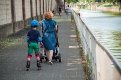Portrait of woman with children in roller skate with protection in border channel stock image