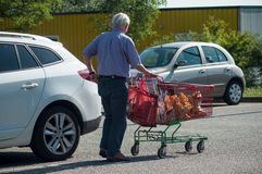 Old man walking with trolley on supermarket parking. Mulhouse - France - 21 June 2018 - old man walking with trolley on supermarket parking Stock Photo