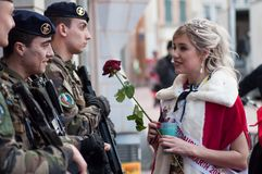 Portrait of miss of carnival speaking to military people with a red rose in hand royalty free stock photo