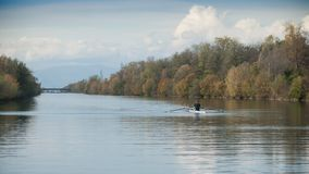 One man  with boat rowing  training on the river in autumn Royalty Free Stock Image