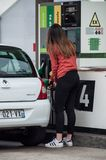 Portrait of young driver girl taking fuel in Intermarche gas Station royalty free stock photos