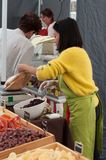 Portrait of asian woman giving dried fruits at the market royalty free stock image