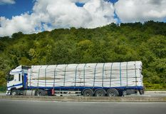 Batten packaged in plastic and loaded in pallet truck. Mulhouse, France - September 15, 2017: Transportation of timber carving wood, sawn timber. Batten packaged stock photos
