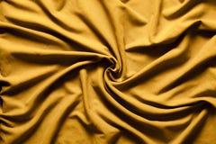 Mulinello dell'oro del tessuto dei drappi Vortice ondulato del fondo immagini stock