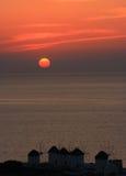 Mulini a vento di MYkonos nell'ambito del tramonto Immagine Stock