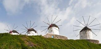 Mulini a vento dietro il fianco di una montagna dell'erba verde immagini stock libere da diritti