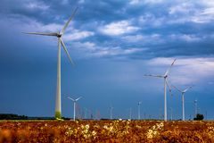 Mulini a vento nei campi con le nuvole di pioggia drammatiche nel backgro immagine stock