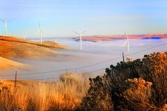 Mulini a vento sopra nebbia Fotografie Stock