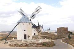 Mulini a vento spagnoli e un castello in La Mancha, Spagna immagine stock libera da diritti
