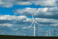 Mulini a vento sulle pianure di Oklahoma sotto un cielo nuvoloso drammatico immagine stock