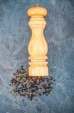 Mulino di pepe e granelli di pepe secchi vicino su Fotografia Stock