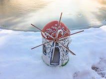 Mulino di vento del ninnolo sulla neve con fondo congelato Immagini Stock Libere da Diritti