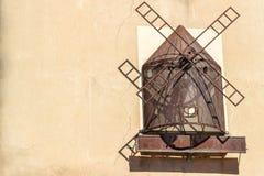 Mulino di vento, scultura del metallo su una parete Rappresentazione di un mulino di vento Immagine Stock Libera da Diritti