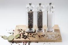 Mulino di vetro con pepe, sale e le spezie sulla a Fotografie Stock