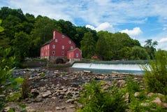 Mulino rosso accanto ad un fiume immagini stock