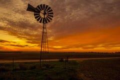 Mulino a vento con la regolazione del sole dietro la Francia Immagini Stock