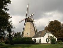Mulino a vento con poca casa Immagini Stock