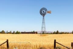 Mulino a vento della pompa idraulica all'azienda agricola del grano nell'Oregon rurale fotografia stock libera da diritti
