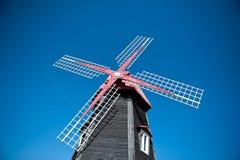 Mulino a vento di legno con un fondo del cielo blu Fotografia Stock