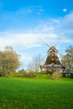 Mulino a vento di legno tradizionale in un giardino fertile Immagini Stock Libere da Diritti
