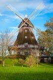Mulino a vento di legno tradizionale in un giardino fertile Fotografia Stock
