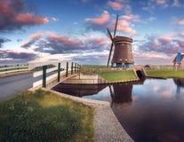 Mulino a vento e ponte vicino al canale dell'acqua ad alba Fotografia Stock