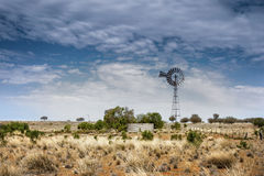 Mulino a vento e punto di innaffiatura su terra rossa su un allevamento di pecore a distanza in Nuovo Galles del Sud occidentale  Immagine Stock