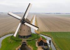 Mulino a vento olandese antico tipico con i campi da sopra fotografia stock libera da diritti