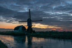 Mulino a vento olandese e vecchia casa lungo un canale dopo il tramonto nell'inverno fotografie stock libere da diritti