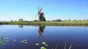 Mulino a vento olandese sopra le acque di fiume archivi video