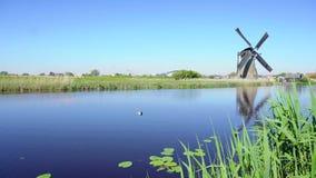 Mulino a vento olandese sopra le acque di fiume video d archivio