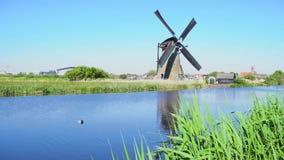 Mulino a vento olandese sopra le acque di fiume stock footage