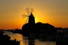 Mulino a vento salino della Sicilia di estate di marsala di tramonto fotografia stock