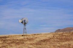 Mulino a vento solo contro cielo blu nel campo asciutto del pascolo fotografia stock libera da diritti