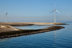 Mulino a vento su una diga Immagine Stock Libera da Diritti