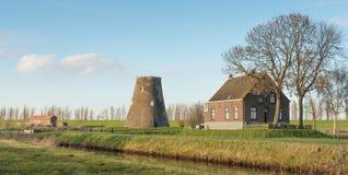 Mulino a vento tronco in un paesaggio rurale Fotografia Stock