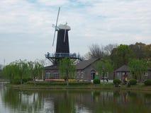 Mulino a vento vicino ad un lago Fotografia Stock Libera da Diritti
